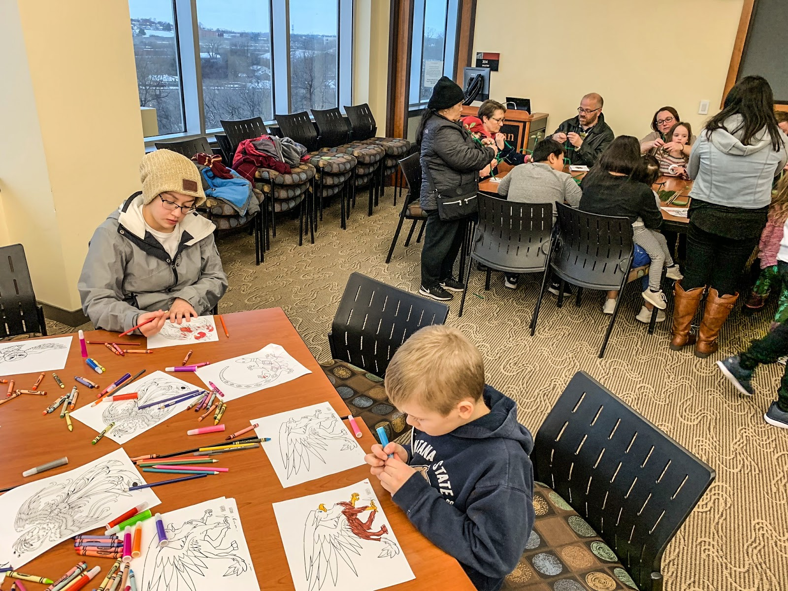 "Participants color magical beasts, foreground, while others construct bowtruckles from green pipe cleaners at ""Beastly Reads,"" a Harry Potter-themed event at the Metropolitan State University Library and Learning Center on Saturday, Dec. 1, 2018. (Photo by J.D. Ganfield / The Metropolitan)"
