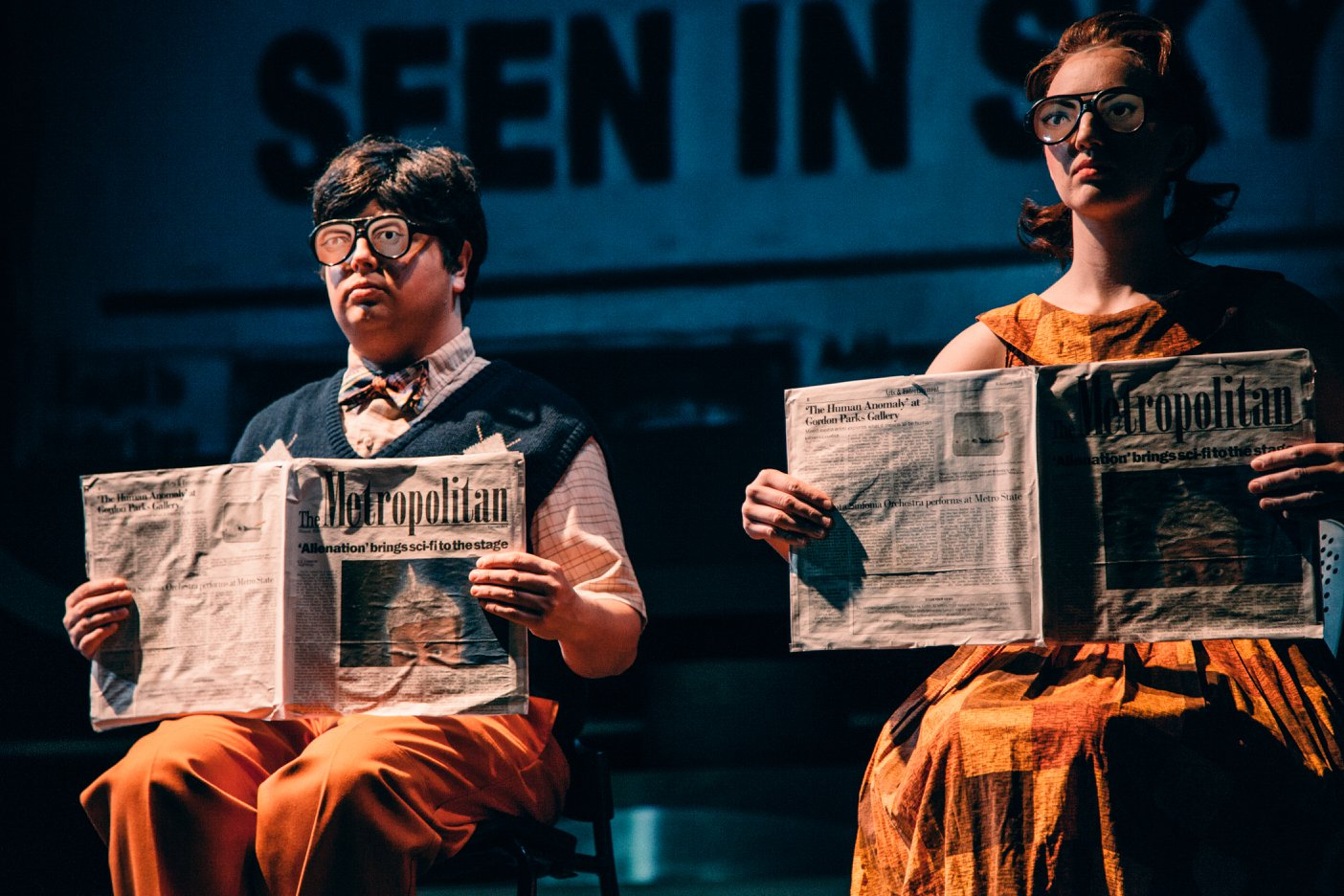 "Maurice Manton, left, and Anna Pladson read copies of The Metropolitan in a scene from ""Alienation,"" a winter 2018 production of Metro State's theater department. (Photo by Matt Benyo)"