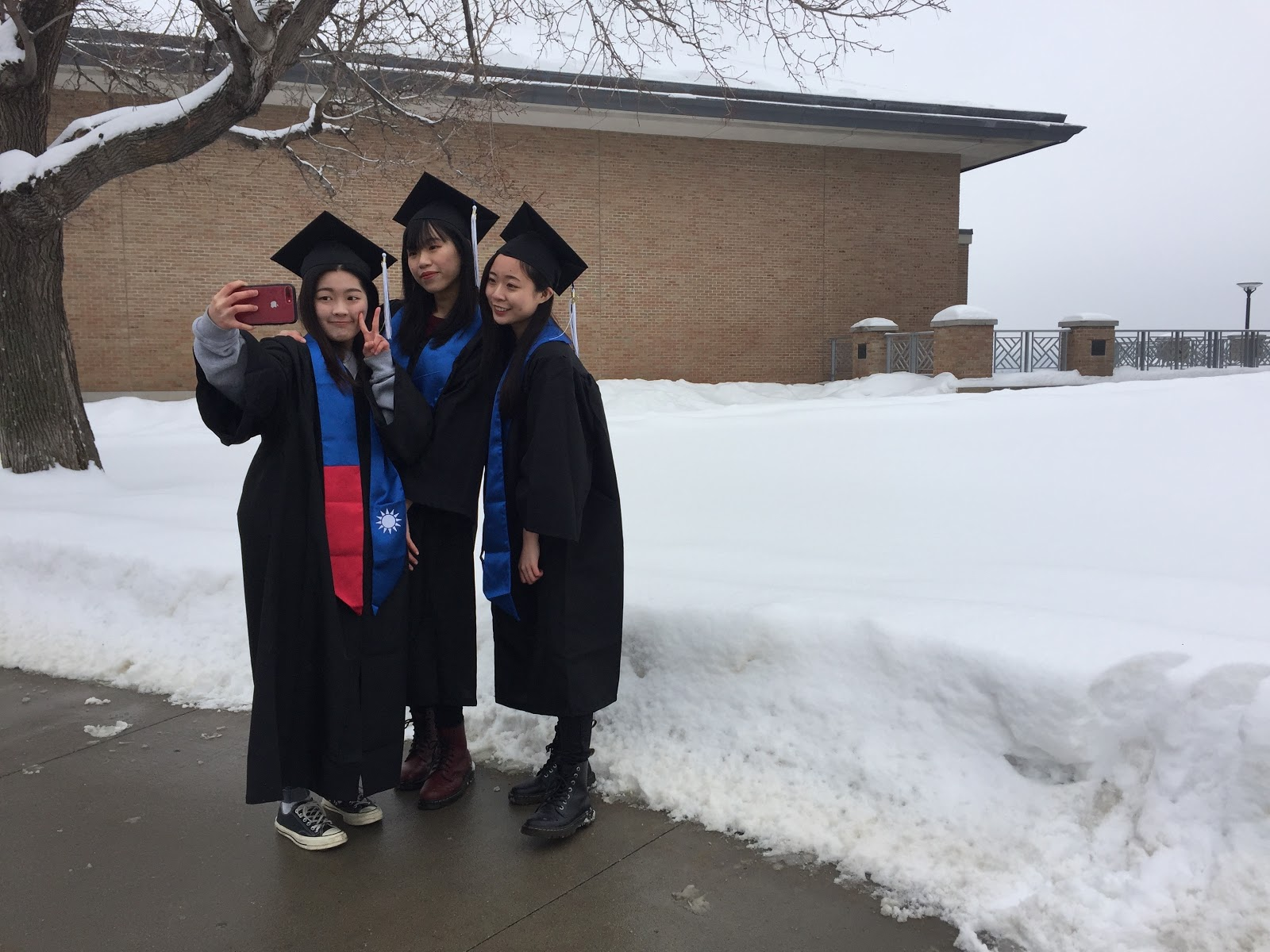 Ya-Hsin Hsueh, left, Chin-Yu Yu and Huei-Cin Chen take selfies in their caps and gowns outside New Main on the St. Paul campus on Saturday, Feb. 23, 2019. The three business administration majors graduate at the end of spring semester and will walk in the commencement exercises at the Minneapolis Convention Center on April 27. They attended the Grad Expo in the Great Hall to purchase their regalia.   (Photo by Margot M. Barry / The Metropolitan)