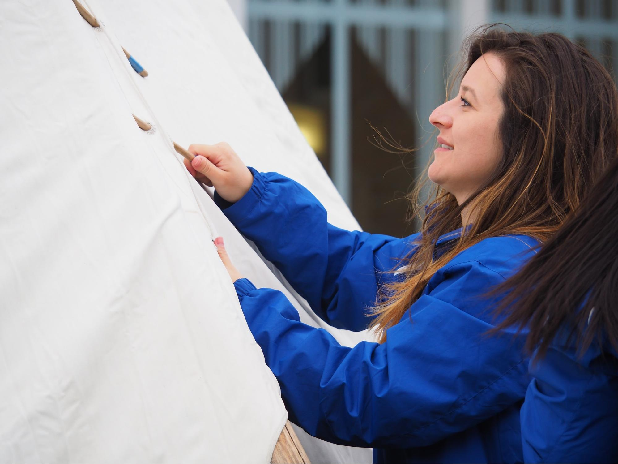 Admissions counselor Sonya Hernandez secures the tipi canvas above the entrance using lacing pins. Event attendees were invited to help Stately raise the tipi. (April Carlson / The Metropolitan)