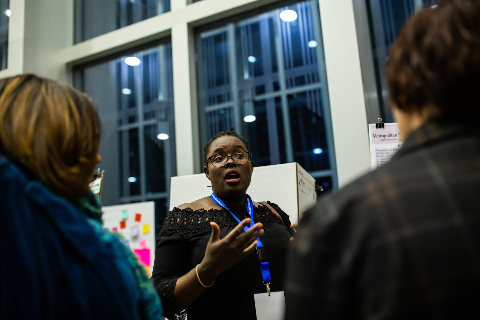 """Doctoral nursing student Survival Mandieka discusses her research, """"Effects of Safe Spaces on Acculturative Stress and Quality of Life in African Young Immigrants,"""" with attendees of the 2018 Student Poster Conference. Photo by Eli Bartz"""