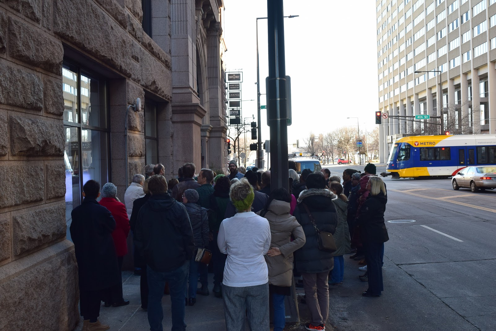 "Visitors cluster around The M's Window Gallery to view David Bowen's ""Waveline."" The museum's new space in the Pioneer Endicott building in downtown St. Paul is located one block from Central Station of the Green Line light rail."