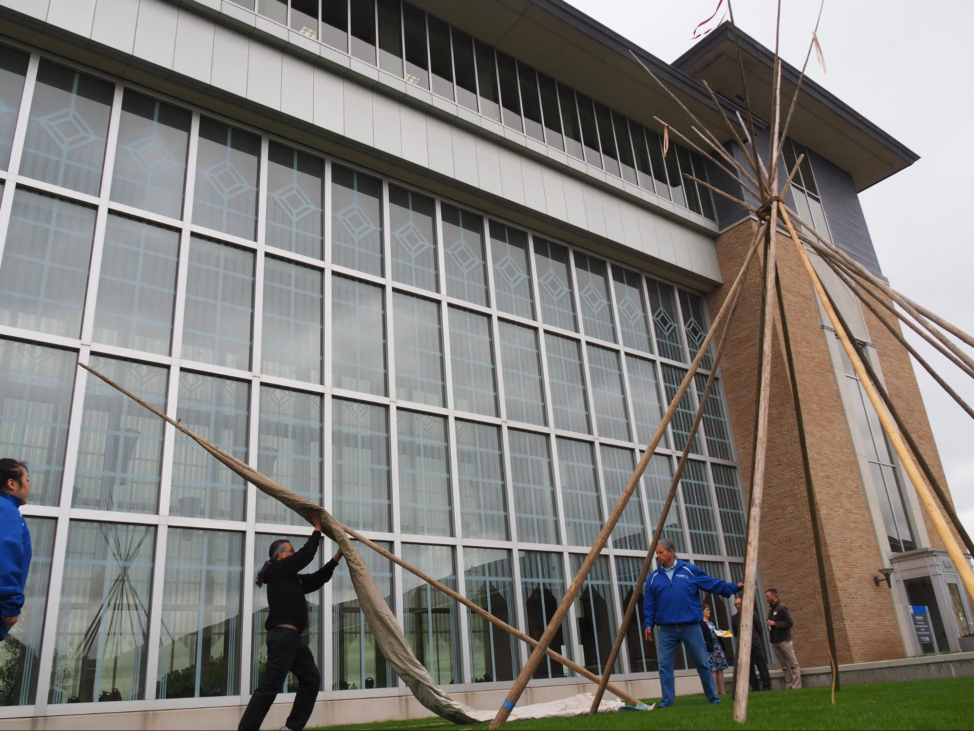 Charlie Stately hoists a lodge pole with the canvas for a tipi on New Main's front lawn on May 23, 2019. The tipi raising opened American Indian Heritage Month activities on Metro State's St. Paul campus. Stately owns Woodland Indian Crafts at the Minneapolis American Indian Center. For the last decade, he has shared his tipis and expertise with the university community. (April Carlson / The Metropolitan)