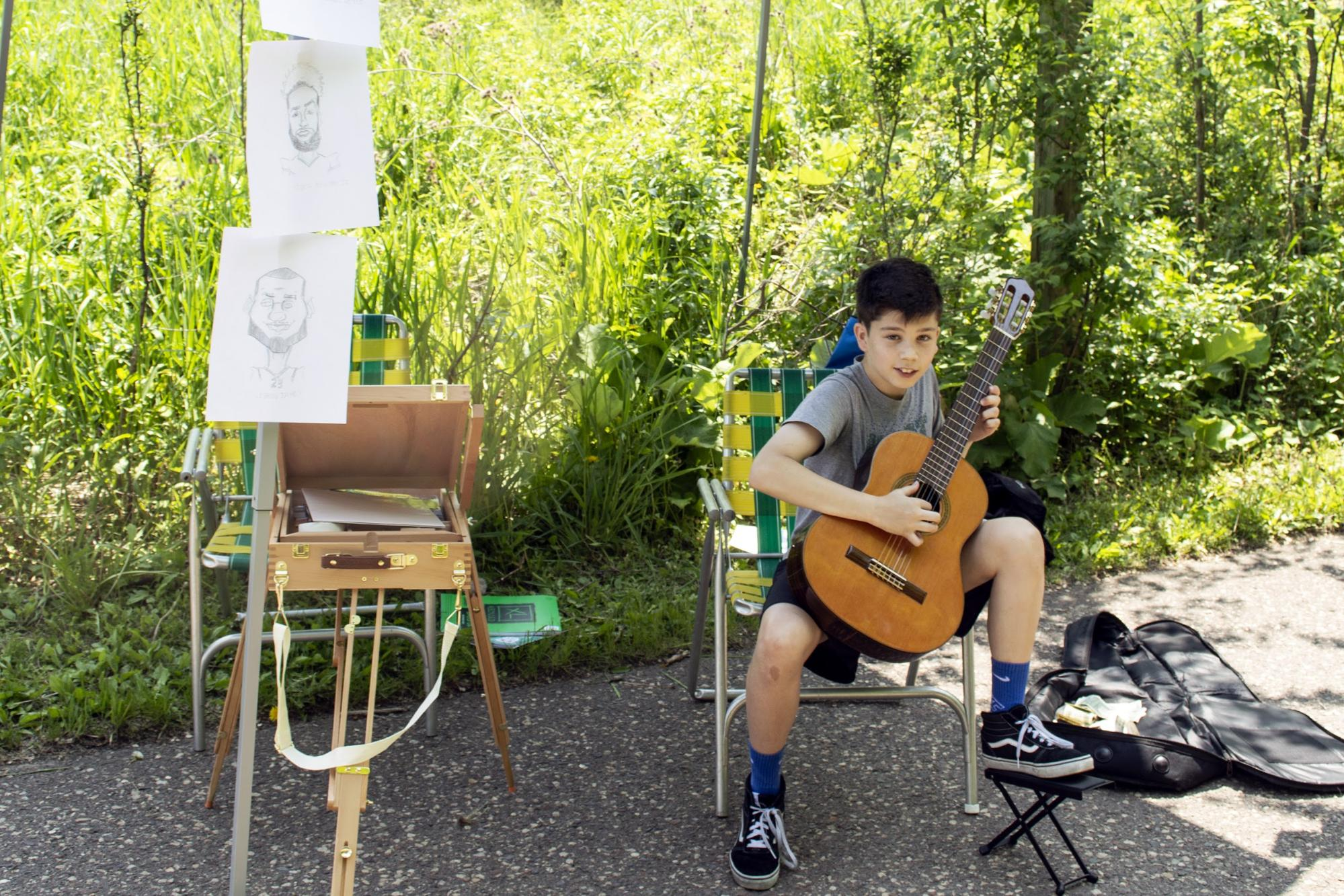 Henry Colin, an 11-year-old artist and musician, plays guitar at Art in the Hollow. Colin also drew caricatures at this year's event. (Mandy Hathaway / The Metropolitan)